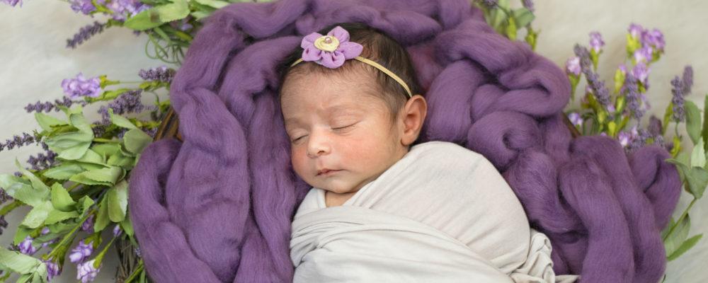 photo of baby sleeping on purple blanket