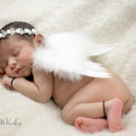 photo of sleeping baby wearing angel wings