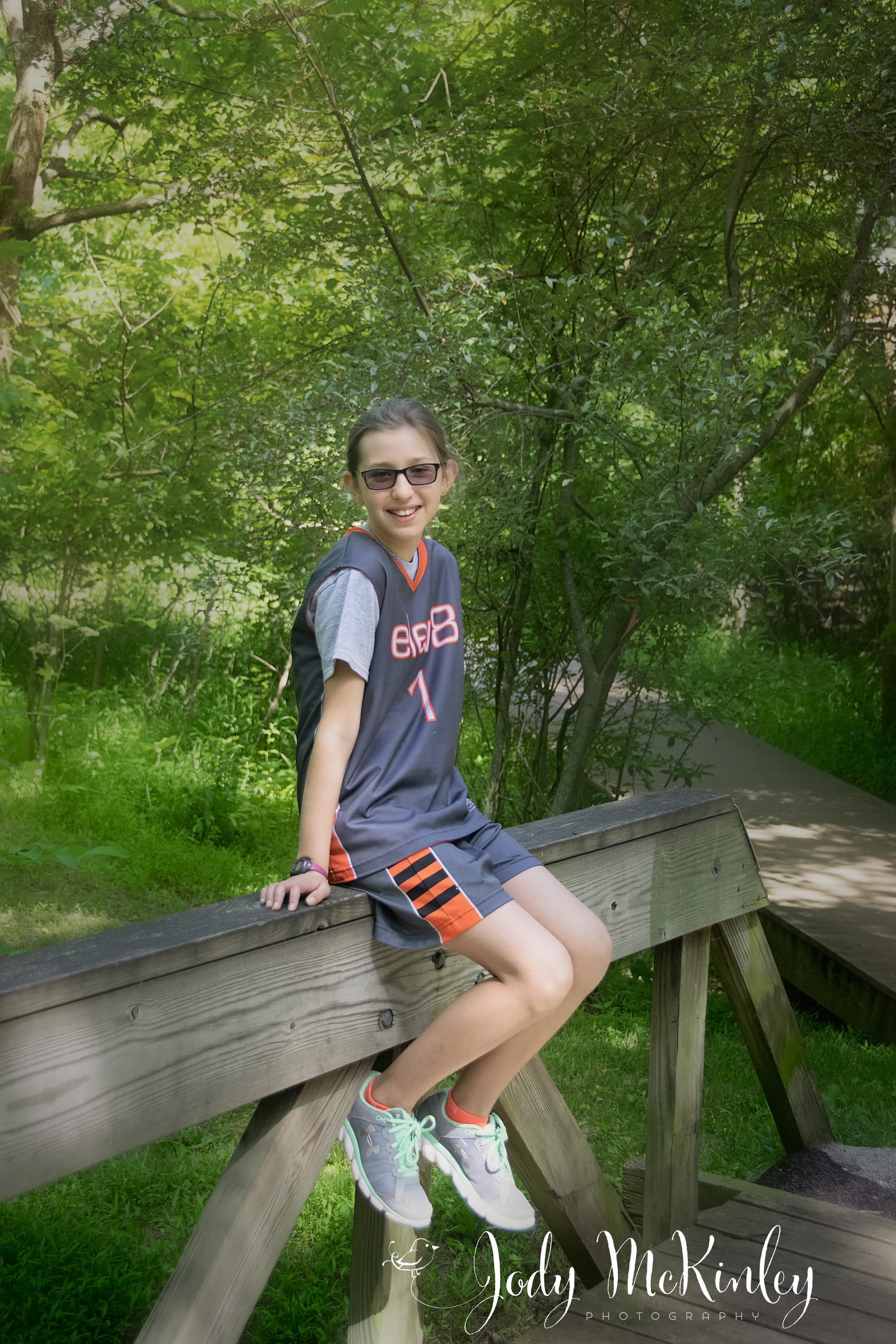 photo of teen girl sitting on wooden bridge railing