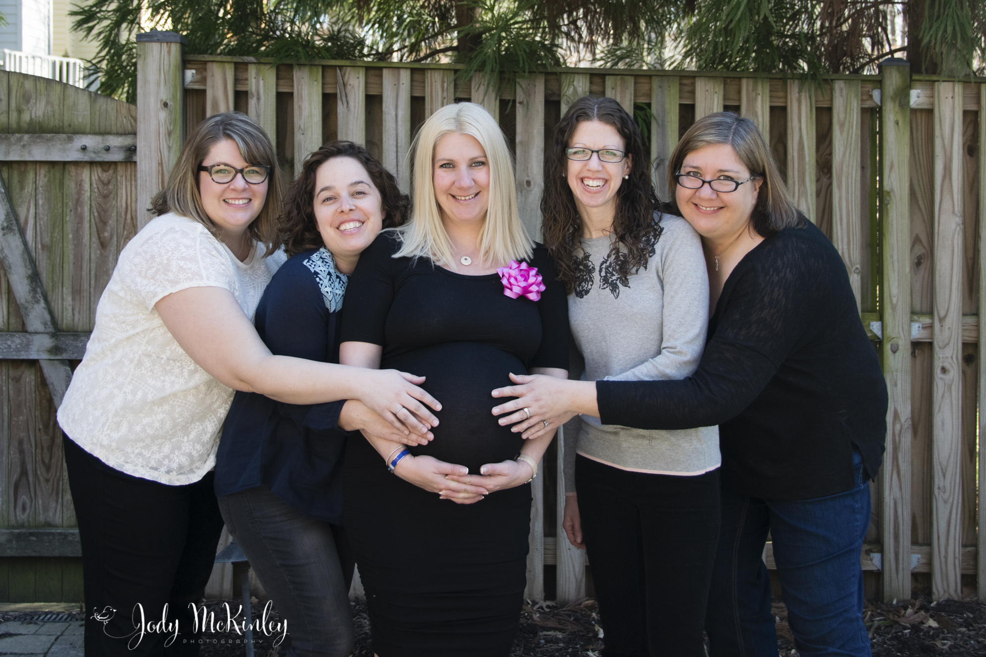 group of woman touching pregnant woman's belly