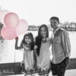 black and white photo of a family holding pink ballonos