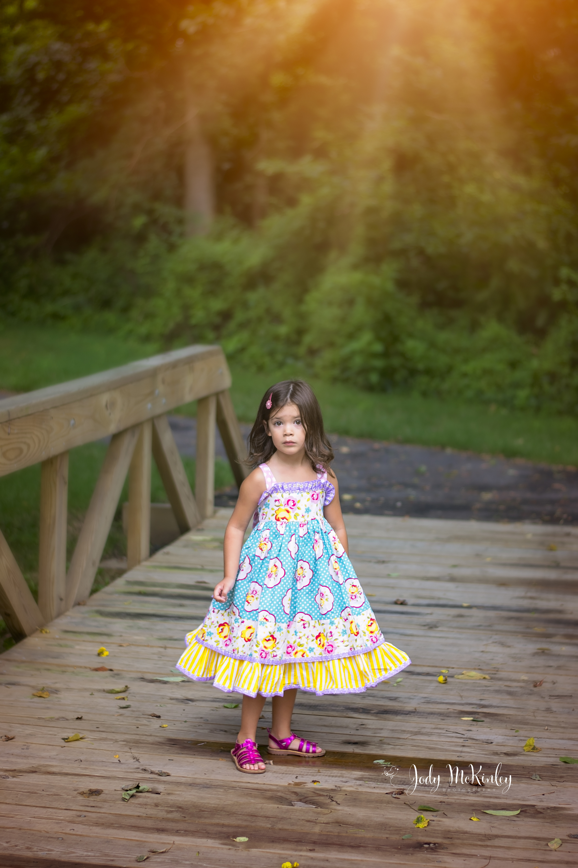 photo of young girl on wooden bridge